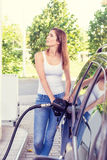 Pretty young woman refuel the car Royalty Free Stock Image