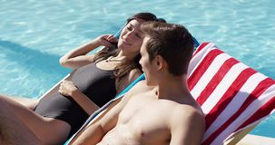 Pretty young woman relaxing with her boyfriend. Pretty young woman smiling and relaxing with her boyfriend in a deck chair alongside a swimming pool as they stock footage