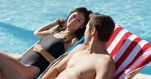 Pretty young woman relaxing with her boyfriend. Pretty young women smiling and relaxing with her boyfriend in a deck chair alongside a swimming pool as they Royalty Free Stock Images