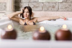 Young woman relaxing in the hot tub. Pretty young woman relaxing in the hot tub stock image