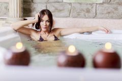 Pretty young woman relaxing in the hot tub Stock Photos