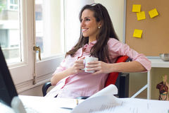 Pretty young woman relaxing one moment in her office. Royalty Free Stock Image