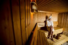Young woman relaxing in the sauna at spa center. Pretty young woman relaxing in the sauna at spa center Royalty Free Stock Images