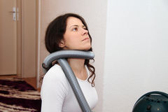 Pretty young woman repairing vacuum cleaner at home. Photo of the Pretty young woman repairing vacuum cleaner at home Stock Image