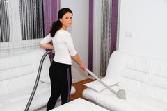Pretty young woman repairing vacuum cleaner at home Royalty Free Stock Photos