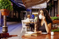 Pretty young woman is resting in cafe terrace and reading book d