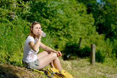 Pretty young woman is resting during a hike in the mountains Royalty Free Stock Image