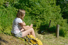 Pretty young woman is resting during a hike in the mountains Stock Photography