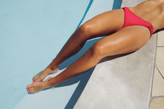 Pretty young woman resting by the poolside Stock Photo