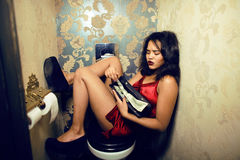 Pretty young woman in restroom with money, like prostitute