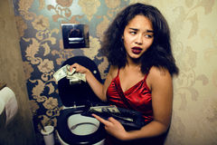 Pretty young woman in restroom with money, like prostitute Royalty Free Stock Images