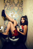 Pretty young woman in restroom with money Royalty Free Stock Images