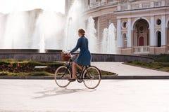 Pretty young woman riding a bike near fountain stock photos