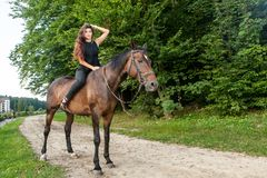 Pretty young woman riding a brown horse Royalty Free Stock Photos