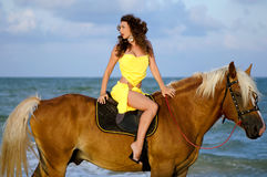 Pretty young woman riding a horse. On the beach Stock Image