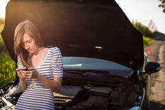 Pretty, young woman by the roadside after her car has broken down stock photography