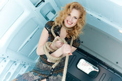 Pretty young woman in ropes in cargo van Stock Image