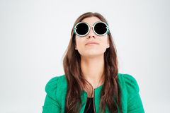 Pretty young woman in round sunglasses looking up stock photography