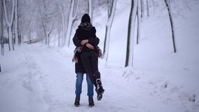 Pretty young woman runs up to the tall man and jumps into his arms in winter park. A man picks up his girlfriend, they. Hug spin around circling. Happy couple stock video footage