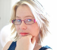 Pretty young woman sad pensive serious face. A close up portrait of a pretty teenage girl wearing spectacles or eye glasses, in a very pensive, serious mood. Her Royalty Free Stock Photos