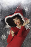 Pretty young woman in Santa Claus clothes. On snowy backgraound Stock Photo