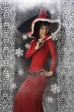 Pretty young woman in Santa Claus clothes. On snowy backgraound Stock Photos