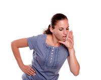 Pretty young woman screaming something down. On blue shirt on isolated background - copyspace Stock Photo