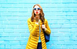 Pretty young woman sends an air kiss on blue background. Pretty young woman sends an air kiss on a blue background Royalty Free Stock Images