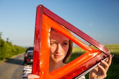 Pretty, young woman setting the safety triangle on the roadside stock photos