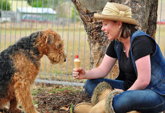 Pretty young woman sharing icecream with dog. A wonderful moment captured of a portrait of a lovely young girl sitting with her pet purebred pedigree Airedale royalty free stock image