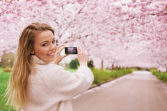 Pretty young woman shooting spring blossom park Stock Photo