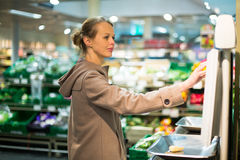 Pretty, young woman shopping for fruits and vegetables Royalty Free Stock Photo