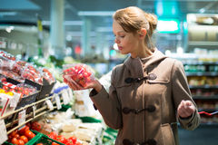 Pretty, young woman shopping for fruits and vegetables Stock Photos