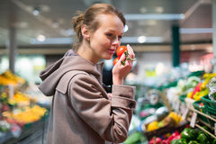Pretty, young woman shopping for fruits and vegetables Stock Image