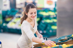 Pretty, young woman shopping for fruits and vegetables in produc Stock Image