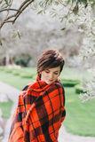 Pretty young woman with short haircut standing in a park wrapped in a warm blanket Stock Photography