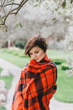 Pretty young woman with short haircut standing in a park wrapped in a warm blanket Royalty Free Stock Photography
