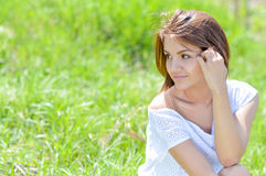 Pretty young woman in short white summer dress on green grass Royalty Free Stock Image