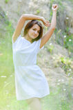 Pretty young woman in short white summer dress on green grass outdoors Royalty Free Stock Image