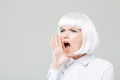 Pretty young woman shouting and calling for somebody Royalty Free Stock Images