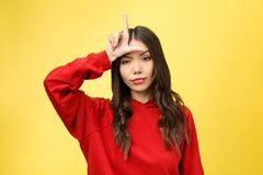 Pretty young woman showing phone sign with her fingers. Colorful studio portrait with yellow background. royalty free stock image