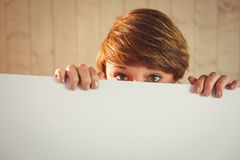 Pretty young woman showing sign hiding her face behind sign Royalty Free Stock Photo