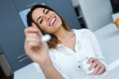 Pretty Young Woman Showing Yogurt To Camera While Eating In The Kitchen At Home Royalty Free Stock Photography