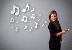 Pretty young woman singing and listening to music with musical n Royalty Free Stock Image