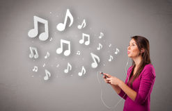 Pretty young woman singing and listening to music with musical n Royalty Free Stock Photo
