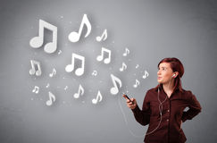 Pretty young woman singing and listening to music with musical n. Otes getting out of her mouth Royalty Free Stock Photography