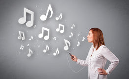 Pretty young woman singing and listening to music with musical n Royalty Free Stock Photos