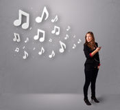 Pretty young woman singing and listening to music with musical n. Otes getting out of her mouth Royalty Free Stock Photo