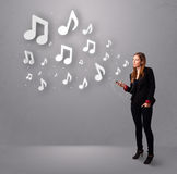 Pretty young woman singing and listening to music with musical n. Otes getting out of her mouth Stock Photo