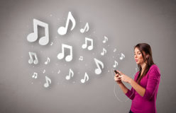 Pretty young woman singing and listening to music with musical n Stock Photo